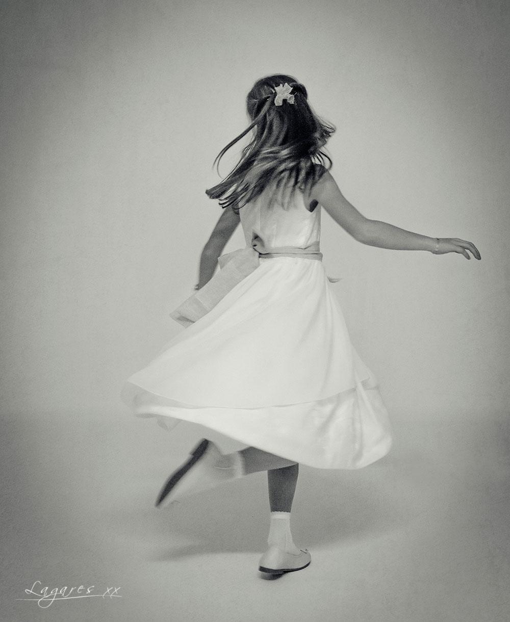 Reportajes de comunión creativos en estudio y exterior por José Luis Lagares, fotógrafo de Cornellá Barcelona y Lloret de mar Girona. Niña de comunión bailando en blanco y negro