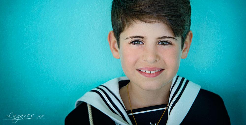 Reportajes de comunión creativos en estudio y exterior por José Luis Lagares, fotógrafo de Cornellá Barcelona y Lloret de mar Girona. Niño de comunión vestido de marinero en pared azul turquesa
