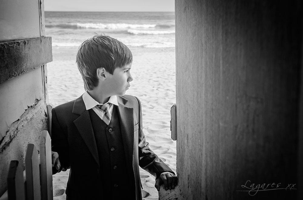 Reportajes de comunión creativos en estudio y exterior por José Luis Lagares, fotógrafo de Cornellá Barcelona y Lloret de mar Girona. Niño de comunión en caseta de baño en la playa en blanco y negro