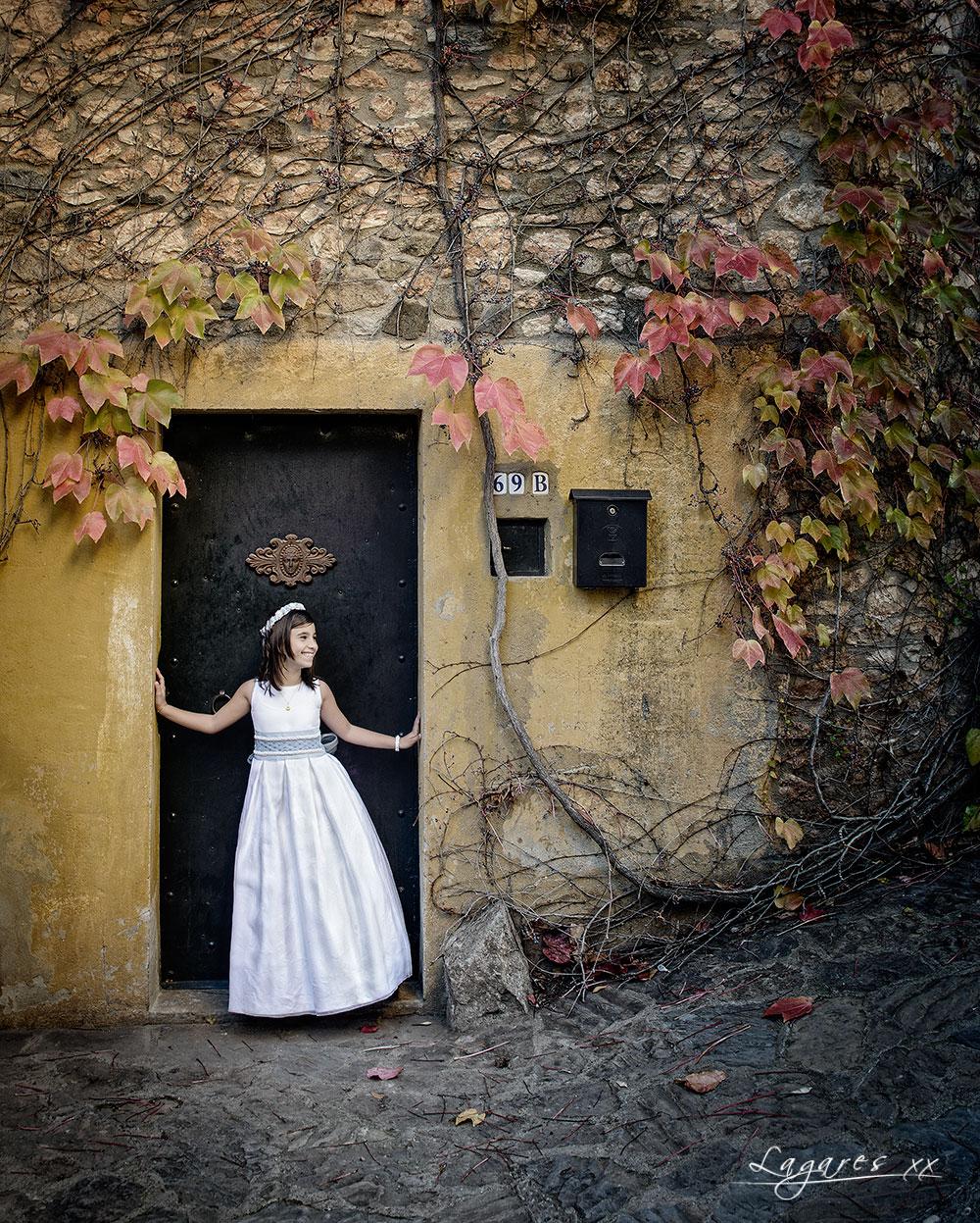 Reportajes de comunión creativos en estudio y exterior por José Luis Lagares, fotógrafo de Cornellá Barcelona y Lloret de mar Girona. Niña de comunión en pueblo medieval y puerta rústica