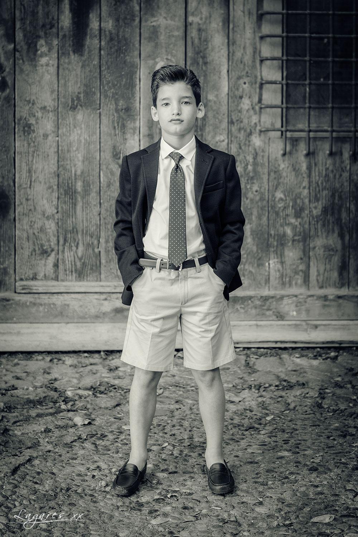 Reportajes de comunión creativos en estudio y exterior por José Luis Lagares, fotógrafo de Cornellá Barcelona y Lloret de mar Girona. Niño de comunión en pueblo rural con pantalón corto blanco y negro