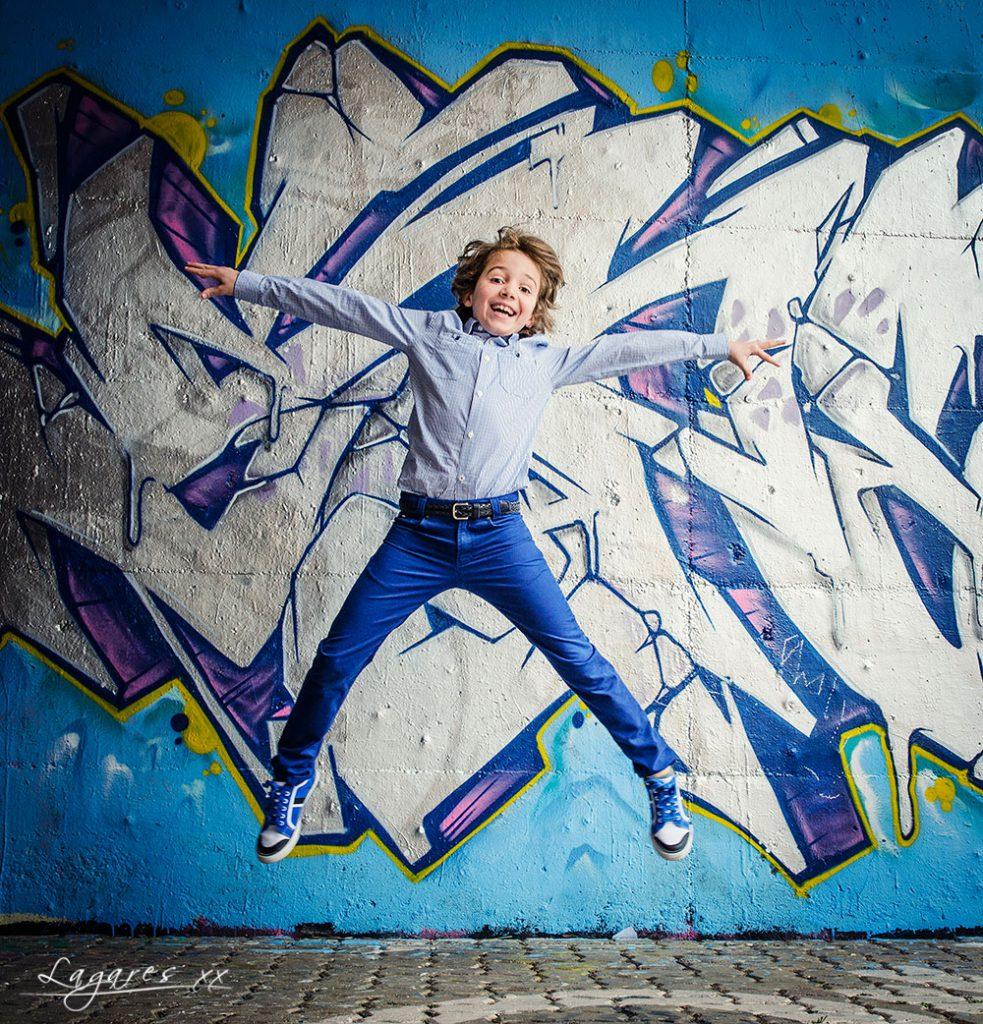 Reportajes de comunión creativos en estudio y exterior por José Luis Lagares, fotógrafo de Cornellá Barcelona y Lloret de mar Girona. Niño de comunión en grafitti saltando con tejano azul