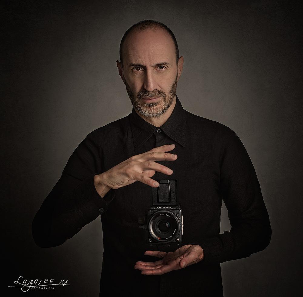 autoretrato del fotógrafo José Luis Lagares en su estudio haciendo levitar una cámara fotográfica marca hasselblad
